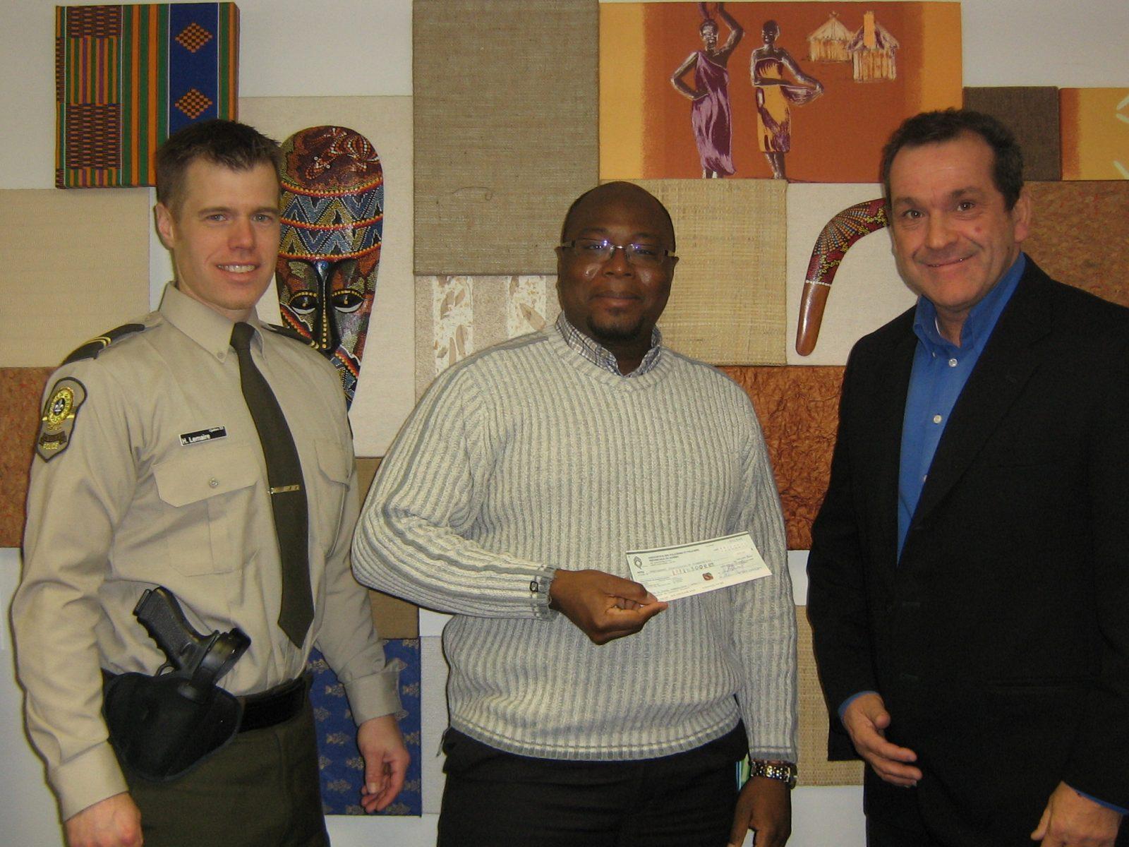 Des policiers de la SQ remettent un chèque de 300$ au Regroupement interculturel de Drummondville